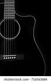 Musical instrument - Silhouette of a black acoustic guitar with cutaway on a black background.