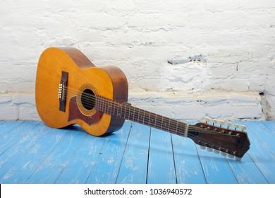 Musical instrument - Vintage twelve-string acoustic guitar on a brick background and blue wooden floor.