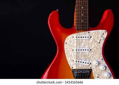 musical instrument wooden six-string guitar red isolated on blackbackground