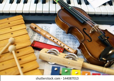 Musical instruments for children: xylophone, children's violin, tambourine, flute, harmonica, piano keyboard.