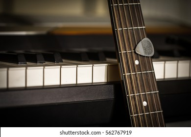 musical instruments piano keys and acoustic guitar with plectrum, closeup, concept, musical composition and creativity