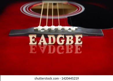 Musical notes EADGBE in corresponding to strings arrangement, with wooden letters, on reflecting surface of an acoustic guitar. Guitars bridge perspective. Creative background.