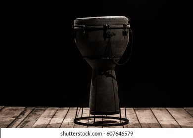 musical percussion instrument drum bongos on a black background ,placed on a wooden floor ,the concept of musical instruments
