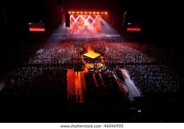 musikalisches Konzert. rotes Licht. Lichtshow. Gruppensängerin tanzt auf der Bühne. helles Licht über der Bühne.