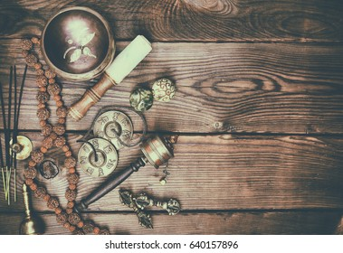Musical religious instruments for Buddhist practices and meditations, brown wood background, empty space on the right, vintage toning