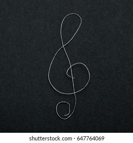musical sign clef made of broken guitar string on black paper