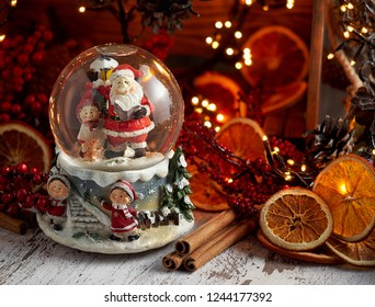 Musical Snow Globe with Santa Claus. Christmas or New Year gift on bokeh background. Close up view, selective focus