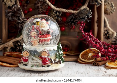 Musical Snow Globe with Santa Claus. Christmas or New Year gift on wooden background. Close up view, selective focus