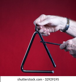 A musical triangle being played by hands isolated against a red background in the square format with copy space.