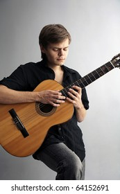 Musican with wooden acoustic guitar playing ballads