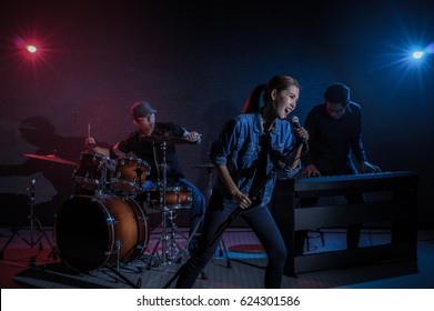Musician band hand holding the microphone and singing a song and playing music instrument with Fellow band musicians on black background with spot light and lens flare, musical concept