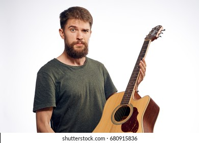 Musician with a beard holds a guitar on a light background music