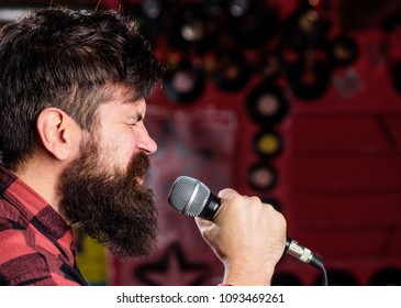 Musician with beard and mustache singing song in karaoke. Punk rock concept. Man with tense face holds microphone, singing song, club background, side view. Guy likes to sing in aggressive manner