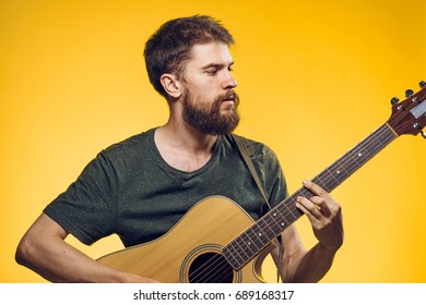Musician with a beard on a yellow background, playing a guitar
