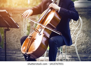 Musician in a black suit sitting on a white elegant chair on the terrace in the Park and playing classical music on string-bow the instrument - cello.