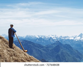 Musician blowing alphorn on the top of mountain in Switzerland.