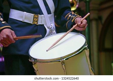 A musician from a brass band plays a set of side drums