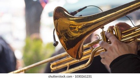 Musician with brass trumpet plays, pressing the valves with his fingers, classical music. Close up view with details, blurred background.