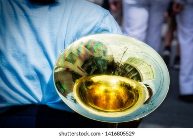 A musician carrying her French horn though the street following a parade in Shimoda, Japan.