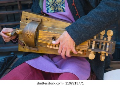 A musician dressed in the medieval costume playing hurdy-gurdy. Horizontal view.