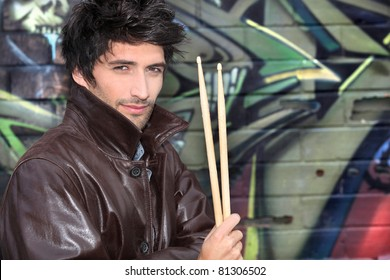 musician with drumsticks against graffiti wall