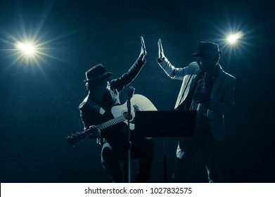 Musician Duo band doing Hand coordination when playing a Trumpet and singing a song and playing the guitar on black background with spot light and lens flare, musical concept