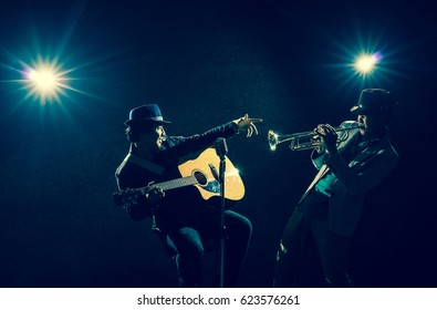 Musician Duo band playing a Trumpet and singing a song and playing the guitar on black background with spot light and lens flare, musical concept