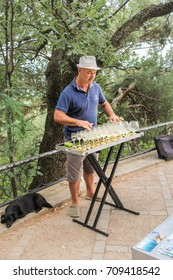 The musician extracts sounds from glasses. Yalta, Crimea - 11 July, 2017. Lush vegetation of the Nikitsky Botanical Garden in the Crimea.