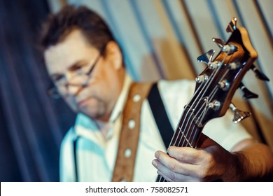 A musician with glasses. A man with a guitar.