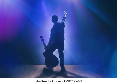 Musician with guitar on stage