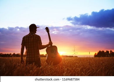 Musician with guitar at sunset field.