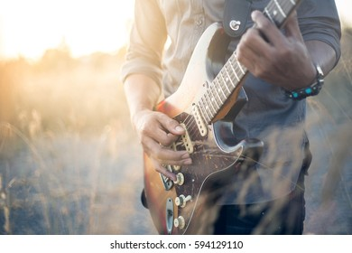 musician with guitar at sunset field, music background, Vintage Style