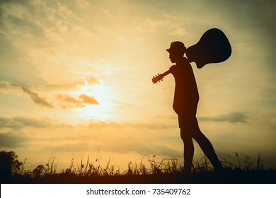 Musician holding acoustic guitar and walking in summer fields with sunset