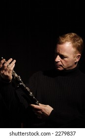 musician holding a clarinet isolated against black background