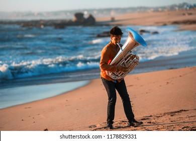 Musician instrumentalist playing the Tuba on the sea coast.