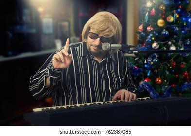 Musician in light yellow wig sits at the electric piano. Middle-aged man is gesticulating. He asks to wait a minute. Do not rush and he will play the required song. Christmas tree stands on the side