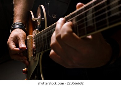 musician man playing guitar, close-up shot, dark background