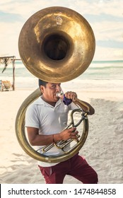 Musician man playing the tuba Blowing hard as to make sound in that instrument