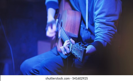 Musician in night club guitarist plays acoustic guitar, close up, telephoto