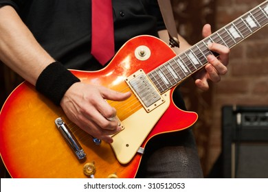 Musician performs solo on electric guitar. Close-up, shallow depth of field
