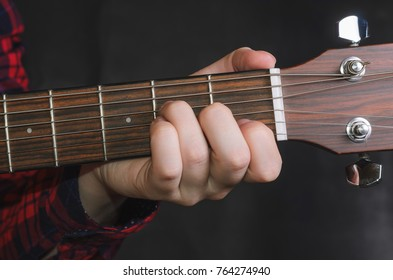 Musician Playing accord Am on acoustic guitar, close up