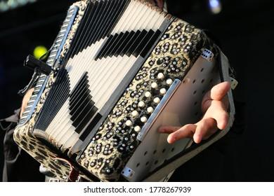 Musician playing an accordian up close.