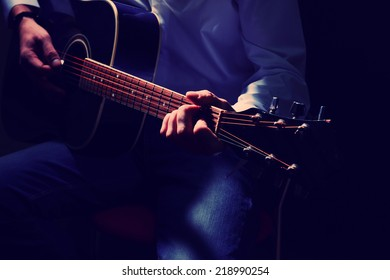 Musician playing acoustic guitar, close up, on dark background