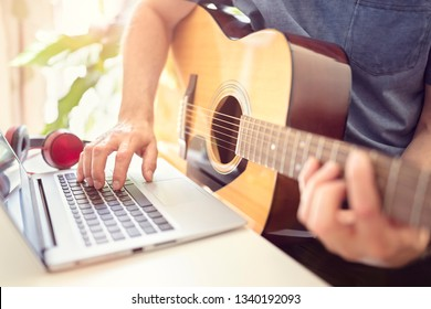 Musician playing acoustic guitar and recording music on computer or learning fom online lesson