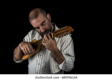 Musician playing the charango, traditional instrument of the Andes. On Black Background