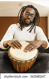 Musician Playing Drum with his hands.