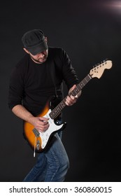 musician playing electric guitar on dark background