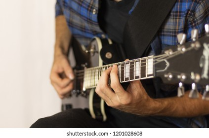 Musician playing  electric guitar in sound recording studio. Rocker playing on electric guitar, closeup.