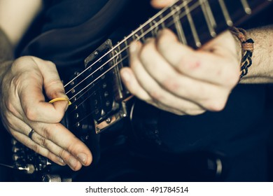 Musician playing electric guitar superstrat type, hands in focus