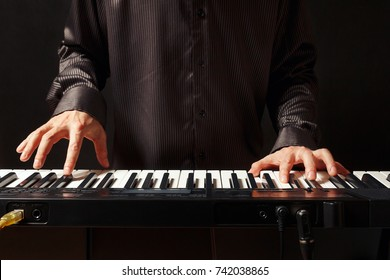 Musician playing the electronic organ on a black background